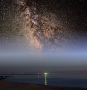 The galactic center above a lighthouse on the Isle of Groix, Brittany, France. Taken from a beach near Larmore Plage.